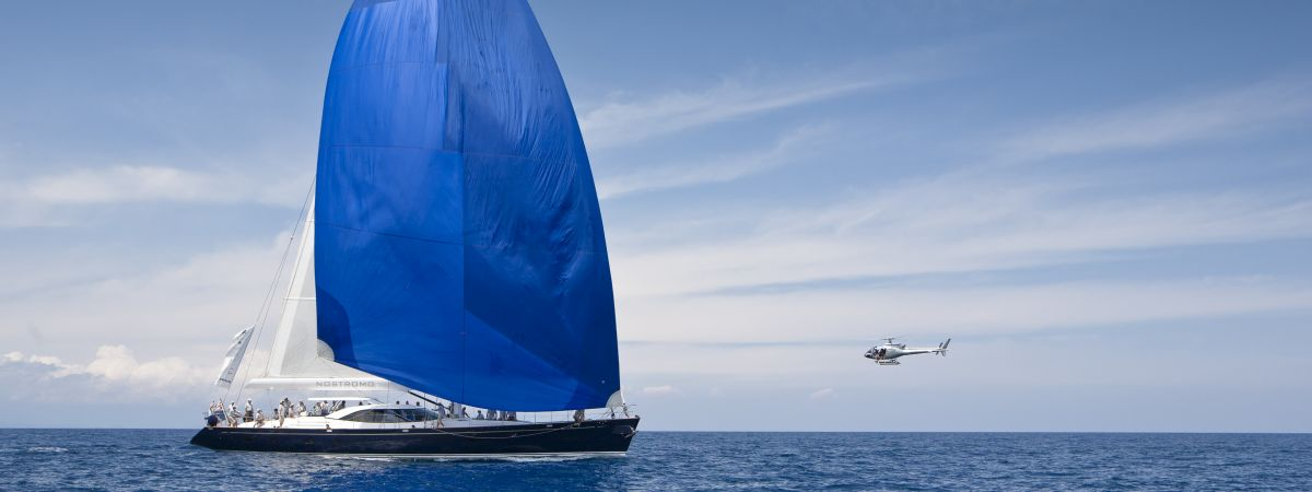 Yacht with blue sail and crew on the open sea